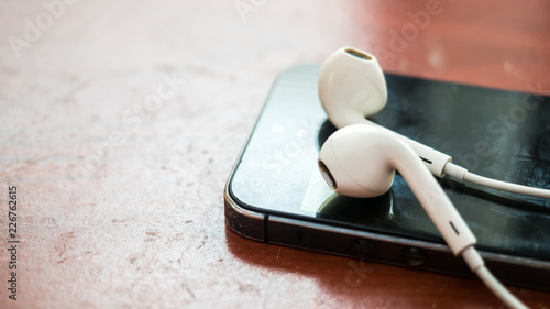 Fototapety, obrazy: earphone on smartphone close up