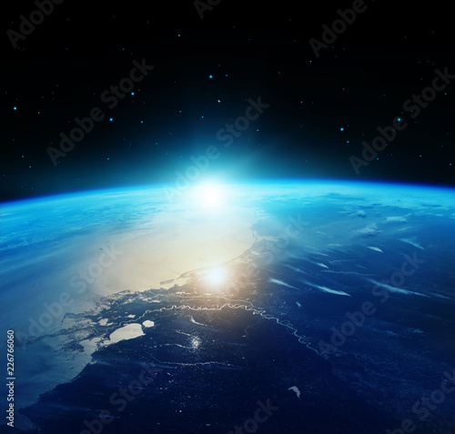 View of blue planet Earth with sun rising from space. Elements of this image furnished by NASA.