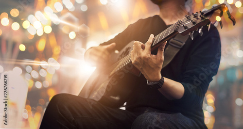 Guitarist on stage and sings in a concert for background, soft and blur concept.