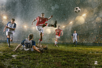 Obraz na płótnie Canvas Soccer players performs an action play on a professional night rain stadium. Dirty players in rain drops scores a goal. Grass in the stadium wet from the rain