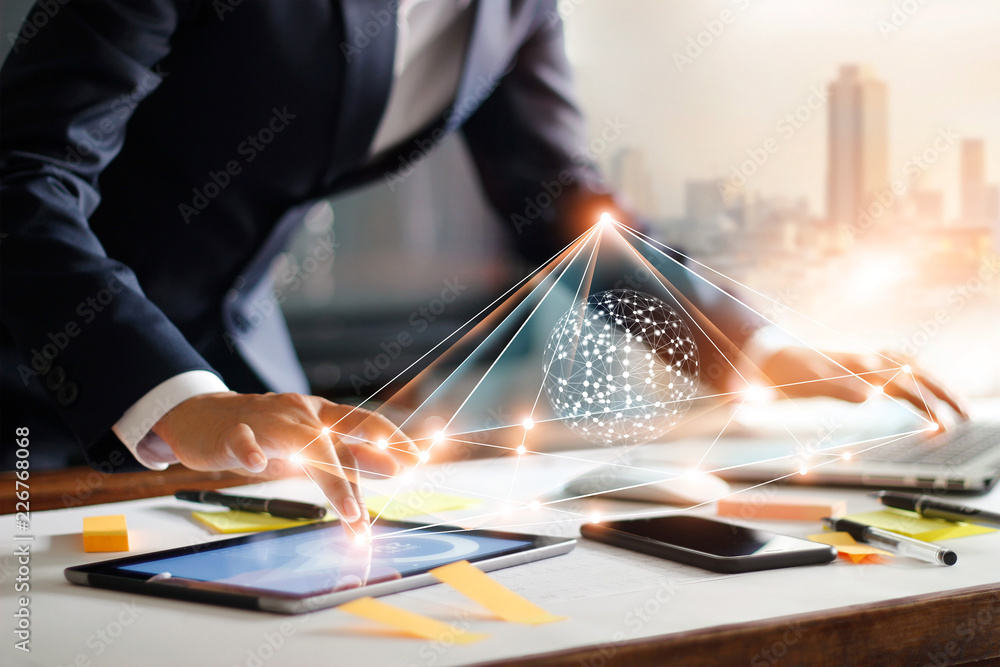 Fototapeta Businessman touching tablet and laptop. Managing global structure networking and data exchanges customer connection on workplace. Business technology and digital marketing.