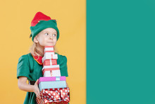 A Little Girl In A Christmas Elf Costume Holding A Stack Of Gift Boxes. Near Empty Place For Text On A Green Background, Copy Space.