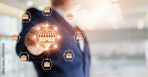 Obraz Businessman hand touching icon global network connection on franchise marketing system. Branch of market and customer. Modern technology business. - fototapety do salonu