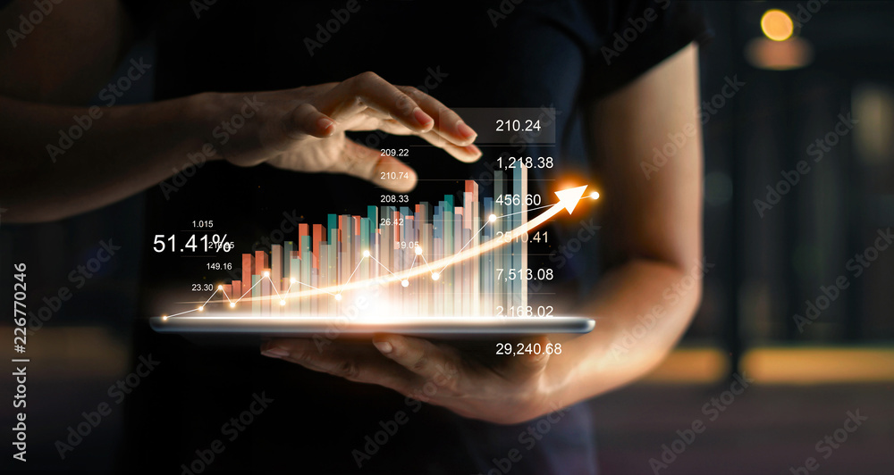 Fototapeta Businessman holding tablet and showing a growing virtual hologram of statistics, graph and chart with arrow up on dark background. Stock market. Business growth, planing and strategy concept.