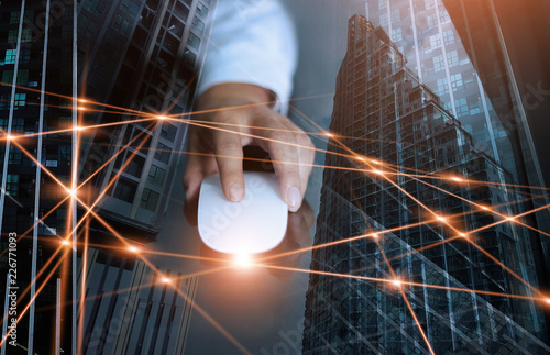 Businessman using mouse global network and data exchanges customer connection on city scape background. Technology business and digital networking concept.