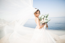 Lovely Bride In White Wedding Dress Posing Near The Sea With Beautiful Background