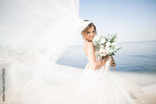 Lovely bride in white wedding dress posing near the sea with beautiful backgroun Fotobehang