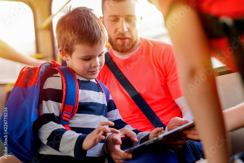 Fotografia  Close up of father and son sitting in a bus and looking at the tablet