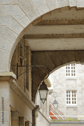 Alignment of street lamps below archways inside the walled city of Saint Malo, B Fototapete