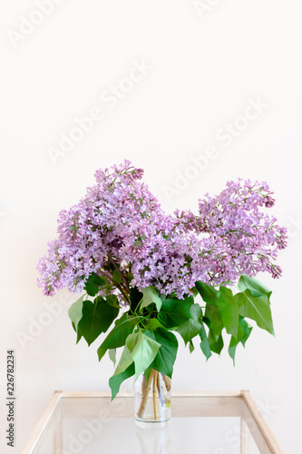 Bouquet of lilac on a glass table