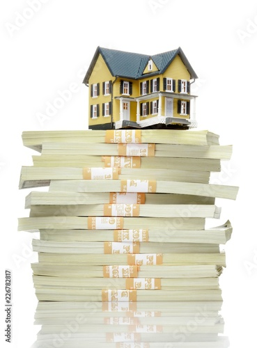 Toy house model on top of dollar stack