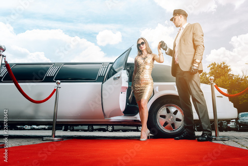 Fotografie, Obraz Driver helping VIP woman or star out of limo on red carpet to a reception