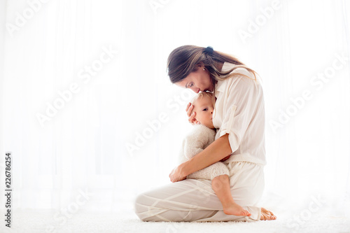 Fotomural  Young mother breastfeeding her toddler baby boy .