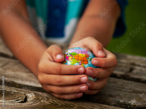Photo  A boy with a ball of the world or planet Earth in his hands