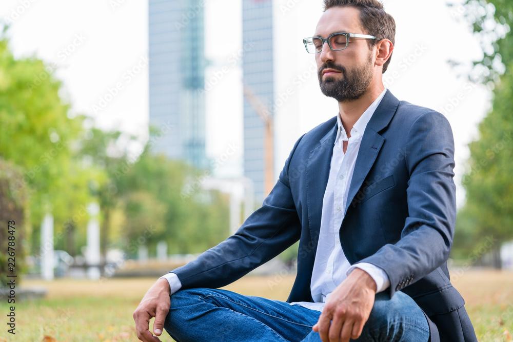 Fototapeta Close-up of calm businessman sitting in the park meditating