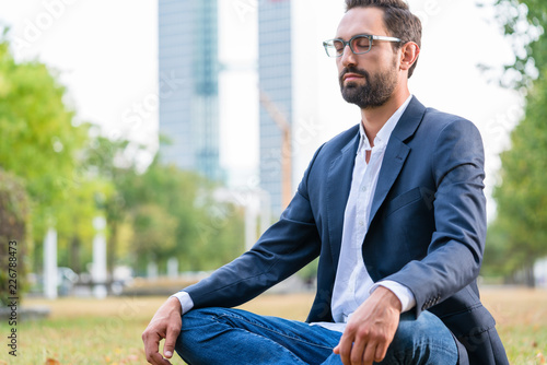 Close-up of calm businessman sitting in the park meditating Billede på lærred