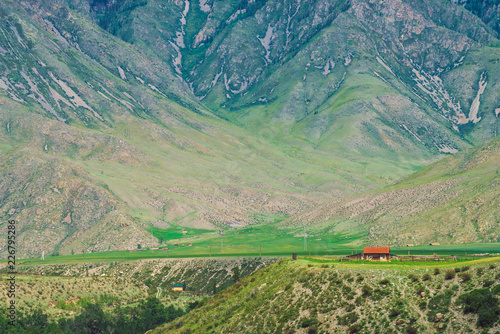 Foto op Canvas Olijf Small lonely village house with red roof near precipice near foot of mountain. Amazing home near abyss with giant mountain slope. Countryside in highlands.