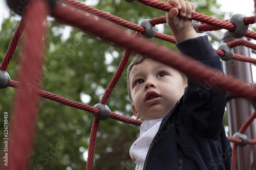 little boy playing in a rope park