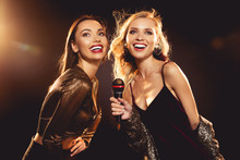 Attractive Cheerful Women Singing With Microphone In Karaoke