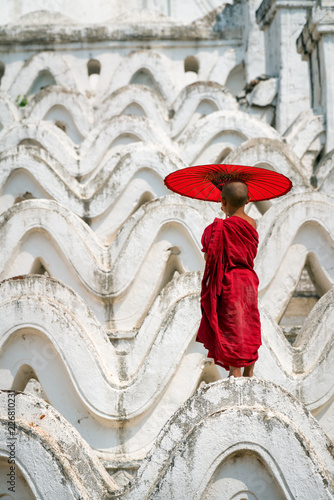 Myanmar Bagan  Novice monk buddhist holding red umbrella  standing on the white pagoda in Bagan Mandalay this is culture in rural of Bagan.