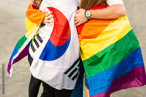 Foto op Canvas Piraten LGBT Community Holding Up Rainbow Flags Proudly To Support Equality And Diversity. Concept Of Supporting The LGBT Community In South Korea, Struggle For Equality Of Sexual Minorities, Hug.