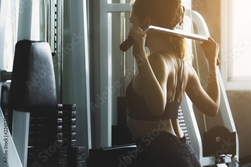 Foto op Aluminium Fitness Closed up young woman working out in modern gym, with sun flare effect reflects on equipment.