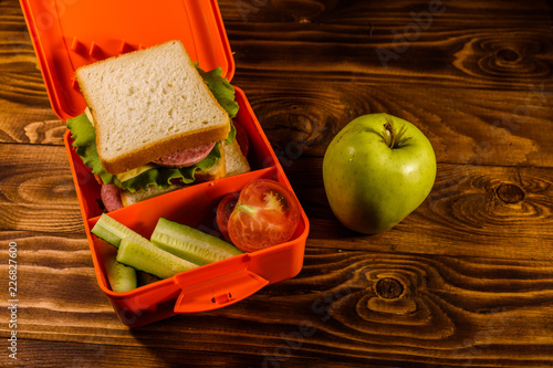 Fotobehang Assortiment Lunch box with sandwich, cucumbers, green apple and tomatoes on wooden table