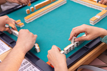 Company Of People Playing Mahjong On Green Table. Hands With Tiles For Playing In Chinese Game. Concept Of Asian, Recreation And Traditional Games, Joint Intellectual Leisure.