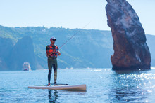 A Man Fishes On A Fishing Tackle In The Standup Paddleboard. Young Fisherman On The SUP Surfing In The Sea Near The Island With Rocks And Mountains.