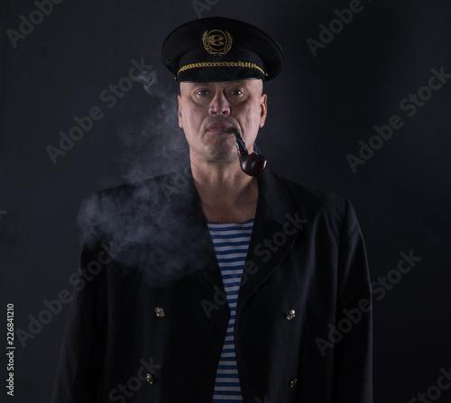 portrait captain of the ship on a black background Fotobehang