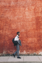 Side View Of Businessman With Backpack Walking On Sidewalk Against Wall In City