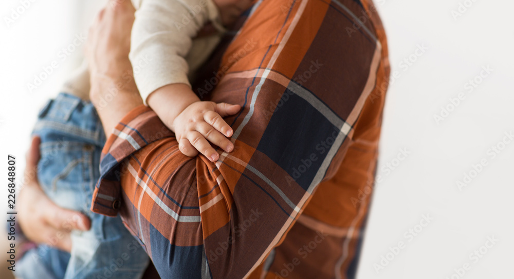 Fototapeta family, fatherhood and people concept - close up of father holding little baby