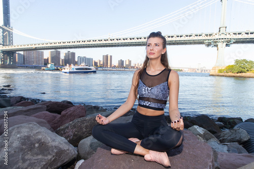 Healthy woman sitting on a rock in the lotus position during yoga exercise