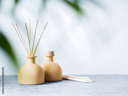 Fototapeta aroma reed diffuser home fragrance with rattan sticks on a light background with palm leaves and shadows. obraz