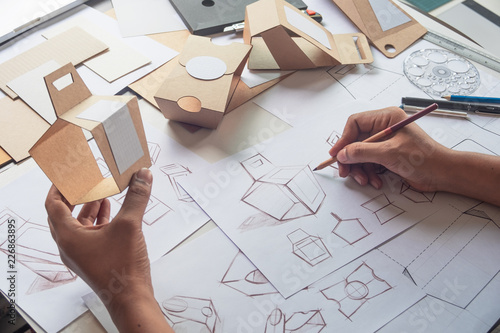 Obraz Designer sketching drawing design Brown craft cardboard paper product eco packaging mockup box development template package branding Label . designer studio concept . - fototapety do salonu