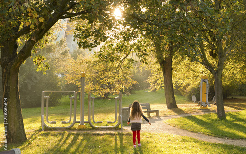 Fototapeta premium Park, siłownia na świeżym powietrzu. Dziewczynka podczas popołudniowego spaceru.