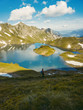"""Tall photographer with heavy backpack point exceptional view of alpine lake """"Schrecksee"""" in the alps with symmetrical reflections in Bavaria, Germany"""