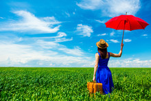 Photo Of Young Beautiful Woman With Suitcase And Red Umbrella In The Field