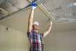 Young handsome man in casual clothing takes measurement of drywall suspended ceiling connected to metal frame on ceiling insulated with aluminum foil. Construction, renovation, DIT concept.