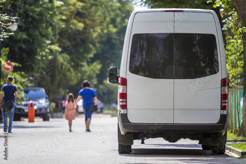 Fototapeta  Back view white passenger medium size commercial luxury minibus van parked on summer city street