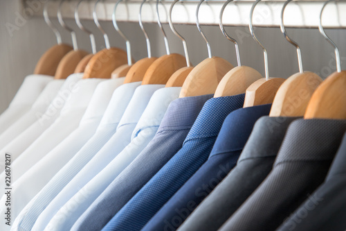 Photo Office Business shirts hanging in a closet ordered by colour