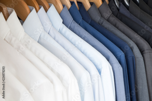 Fotografie, Tablou Office Business shirts hanging in a closet ordered by colour
