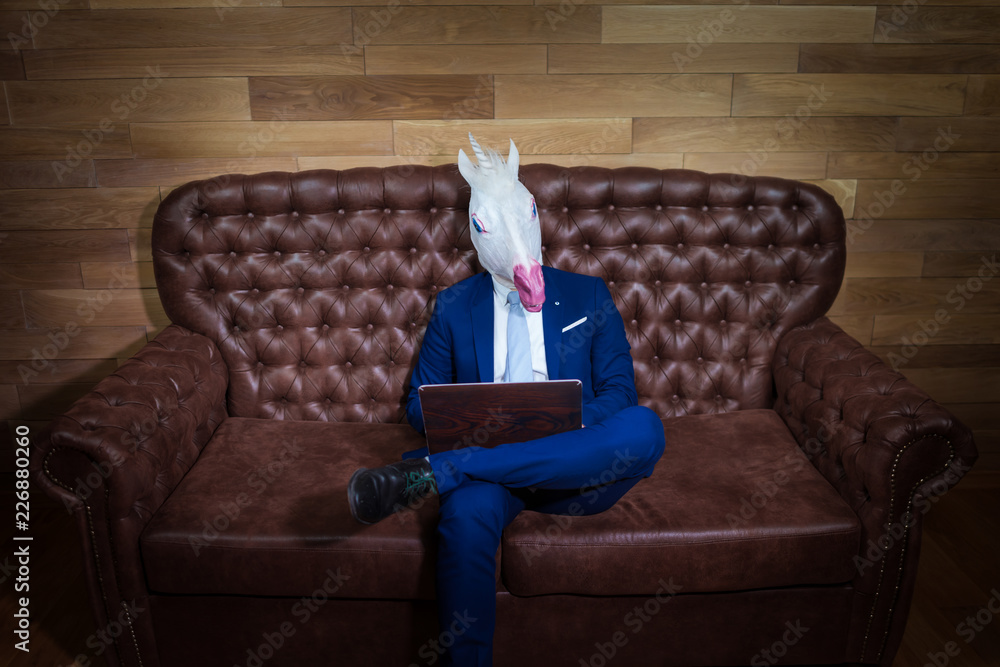 Fototapety, obrazy: Strange man in elegant suit working at home office. Unusual young manager in comical mask on background of wooden wall. Funny unicorn sits on sofa like a boss.