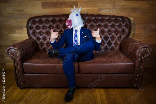 Fototapeta Funny unicorn in elegant suit sits on sofa like a boss and showing gesture thumbs up