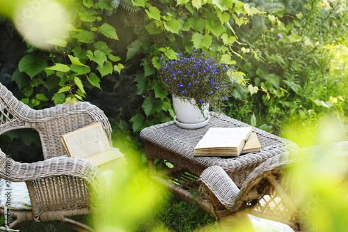 Wicker table, chairs and books in the garden at summer time