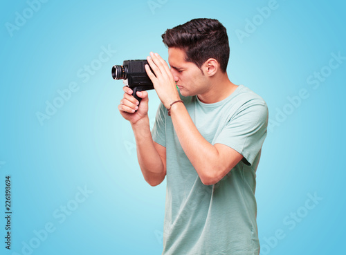 Photo  young handsome tanned man with a vintage cinema camera