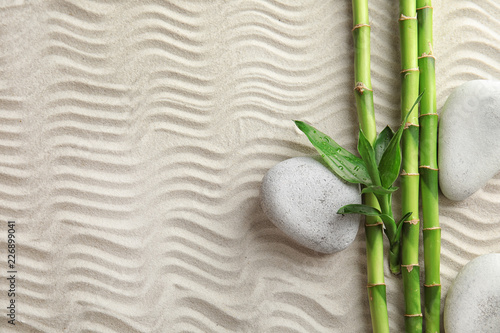 Foto op Plexiglas Stenen in het Zand Bamboo branches with spa stones on sand, top view. Space for text