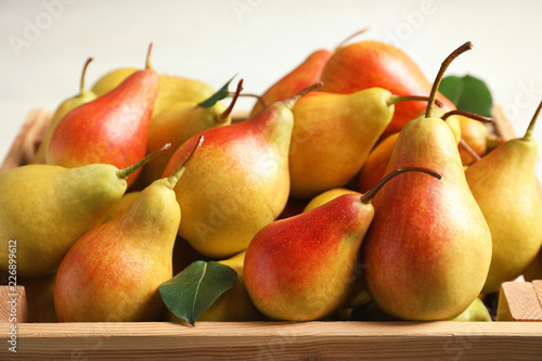 Wooden crate with ripe pears on light background, closeup