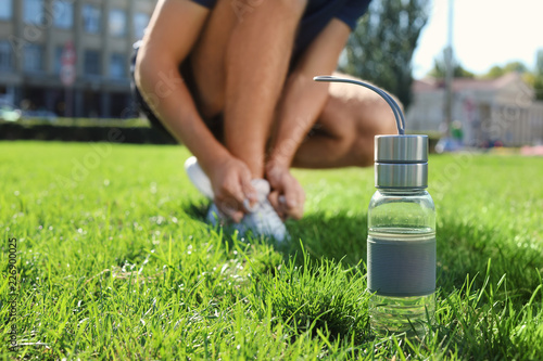 Fotografía  Bottle with water near man lacing his sneakers outdoors