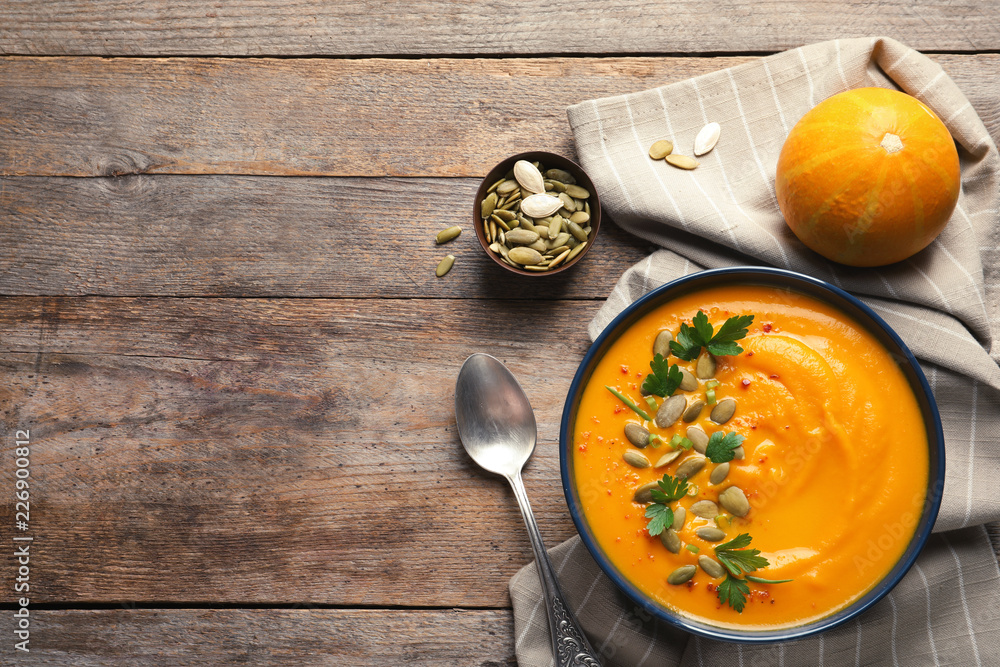 Fototapety, obrazy: Flat lay composition with pumpkin cream soup in bowl on wooden background. Space for text